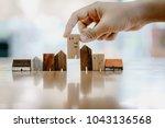hand choosing mini wood house... | Shutterstock . vector #1043136568