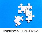 white jig saw puzzle on a blue... | Shutterstock . vector #1043149864