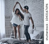 dancing on the bed. full length ... | Shutterstock . vector #1043167696