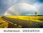 rainbow over rural highway road ... | Shutterstock . vector #1043169214