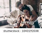 Small photo of You are playing great! Handsome young bearded man teaching his girlfriend to play guitar while both sitting in bed at home together