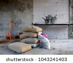 The bags of cement , shovel and cement tub on table in the construction site - stock photo