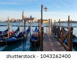 sunset in venice. gondolas at... | Shutterstock . vector #1043262400