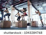 Small photo of Group of sporty muscular people are working out in gym. Cross fit training. Jumping on a box together.