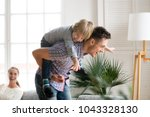 happy dad holding little cute... | Shutterstock . vector #1043328130