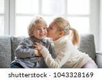 Stock photo older sister embracing little younger brother at home kid girl kissing cute shy smiling preschool 1043328169