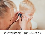 doctor examines ear with... | Shutterstock . vector #1043367559