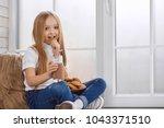 pretty little girl eats cookies ... | Shutterstock . vector #1043371510
