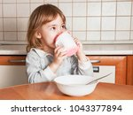 little girl eats and drinks at... | Shutterstock . vector #1043377894