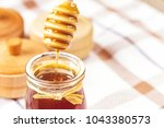viscous liquid honey flows into ... | Shutterstock . vector #1043380573