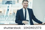 smiling businessman with coffee ... | Shutterstock . vector #1043401573