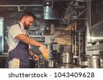 young chef prepares in the... | Shutterstock . vector #1043409628