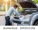 man examining a broken car on a ... | Shutterstock . vector #1043411146