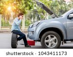 Man call examining a broken car on a sunny day - stock photo