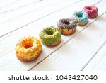 set of donuts on white wooden... | Shutterstock . vector #1043427040