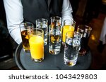 a catering waiter holds a tray... | Shutterstock . vector #1043429803