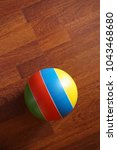 Small photo of A lone striped ball. Multicolored stripes. One object. Isolated. Wooden floor. Brown boards. Shooting from above. Design element.