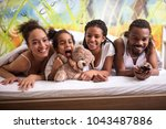 young family in bed together... | Shutterstock . vector #1043487886