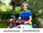 teenager riding scooter.... | Shutterstock . vector #1043494510