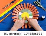 child makes smiling sun from cd.... | Shutterstock . vector #1043506936