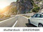 white car rushing along a high... | Shutterstock . vector #1043539684