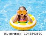 little girl in swimming pool... | Shutterstock . vector #1043543530