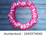 hawaiian wreath on a wooden... | Shutterstock . vector #1043574040