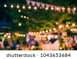 Stock photo abstract blurred image of night festival in garden with bokeh for background usage vintage tone 1043653684