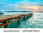 wooden jetty with sunset... | Shutterstock . vector #1043667814