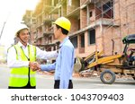 asian engineers shake hands at... | Shutterstock . vector #1043709403