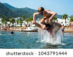daddy throws his child from the ... | Shutterstock . vector #1043791444