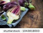 fresh purple artichokes on dark ... | Shutterstock . vector #1043818003