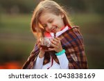 little girl with a cup of hot... | Shutterstock . vector #1043838169