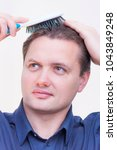 Small photo of Portrait of young Caucasian Ethnicity man with blue shirt brushing combing hair with hairbrush on white background