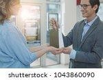 happy female shop assistant... | Shutterstock . vector #1043860090