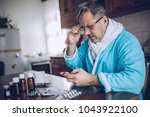 a sick man seated at the table... | Shutterstock . vector #1043922100