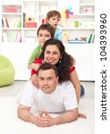 Happy young family portrait - parents and kids joyful heap at home - stock photo