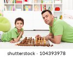 Father and son playing chess - family spending time together - stock photo