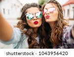 portrait of two ladies with red ... | Shutterstock . vector #1043956420
