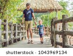 father and son at the zoo.... | Shutterstock . vector #1043969134