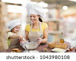 mother and child cooking | Shutterstock . vector #1043980108