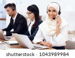 an arab woman works in a call... | Shutterstock . vector #1043989984