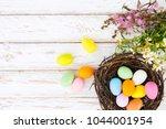 colorful easter eggs in nest...   Shutterstock . vector #1044001954