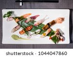 Small photo of mix of different nigiri on a bamboo leaf served with daikon and radish julienne, traditional Japanese food, squid, salmon, swordfish, tuna, lobster, shrimp, prawn, amberjack, roasted eel