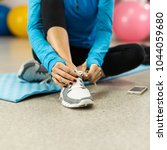 woman tying shoelace before... | Shutterstock . vector #1044059680