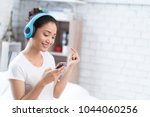 asian women are listening to... | Shutterstock . vector #1044060256