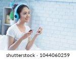 asian women are listening to... | Shutterstock . vector #1044060259