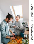 young couple making breakfast... | Shutterstock . vector #1044085654
