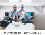 young couple playing video... | Shutterstock . vector #1044088789