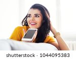 young woman talking on phone on ... | Shutterstock . vector #1044095383